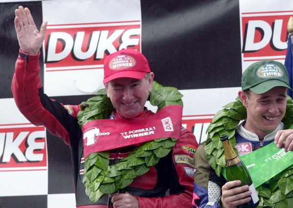 Joey Dunlop waves on the TT podium, 2000 Duke Video Formula 1 TT, with team mate John McGuinness next to him.